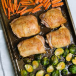 chicken thighs and roasted vegetables on a sheet pan