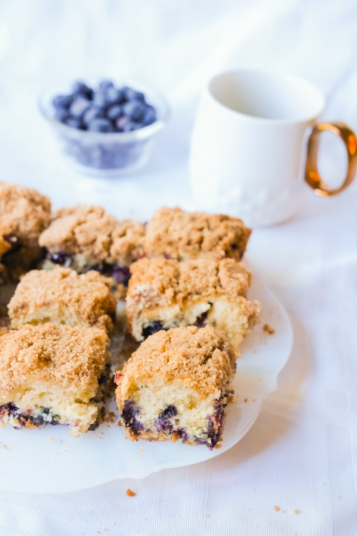 blueberry coffee cake with blueberries and coffee on a kitchen table