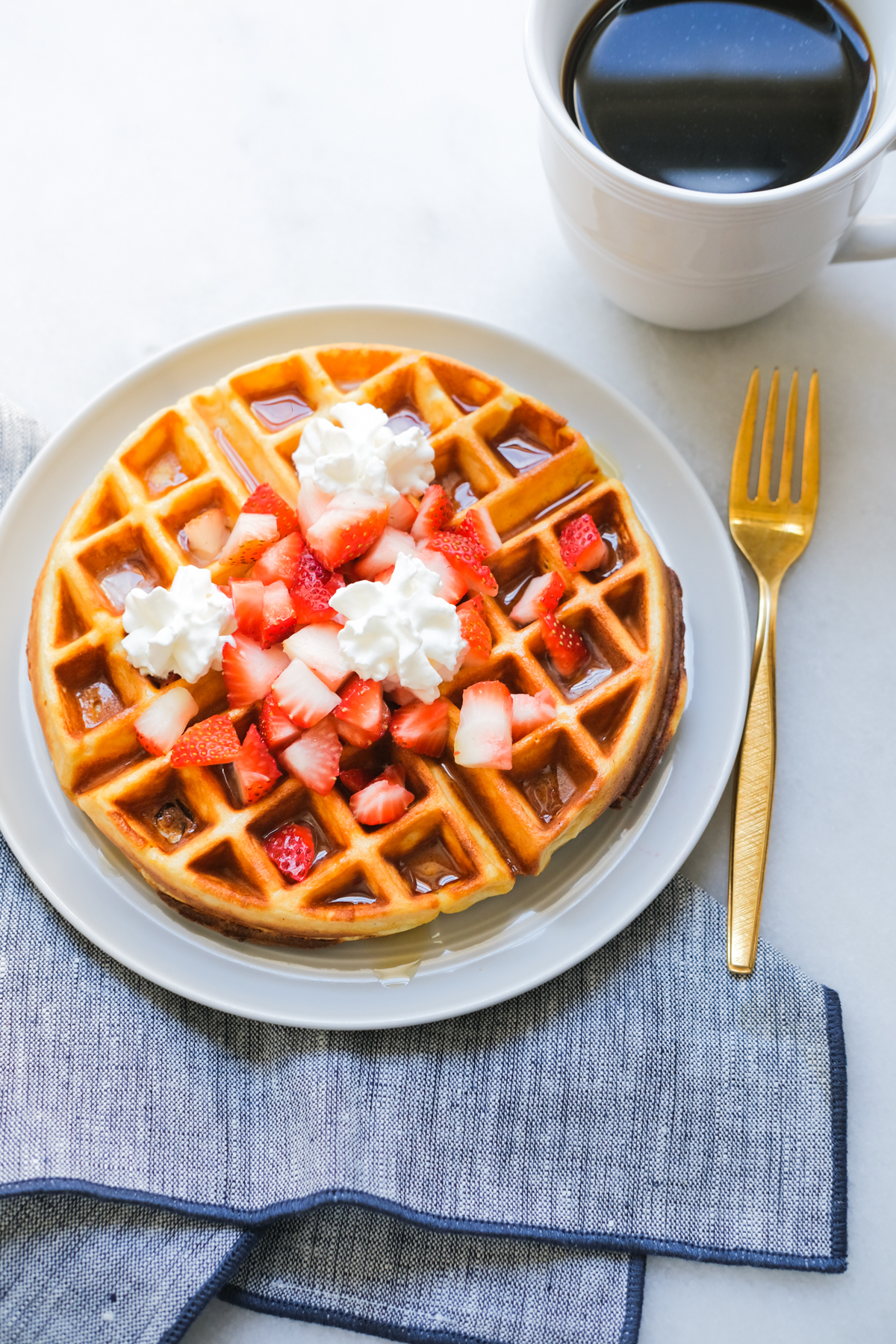 protein waffle with diced strawberries and whipped cream with coffee
