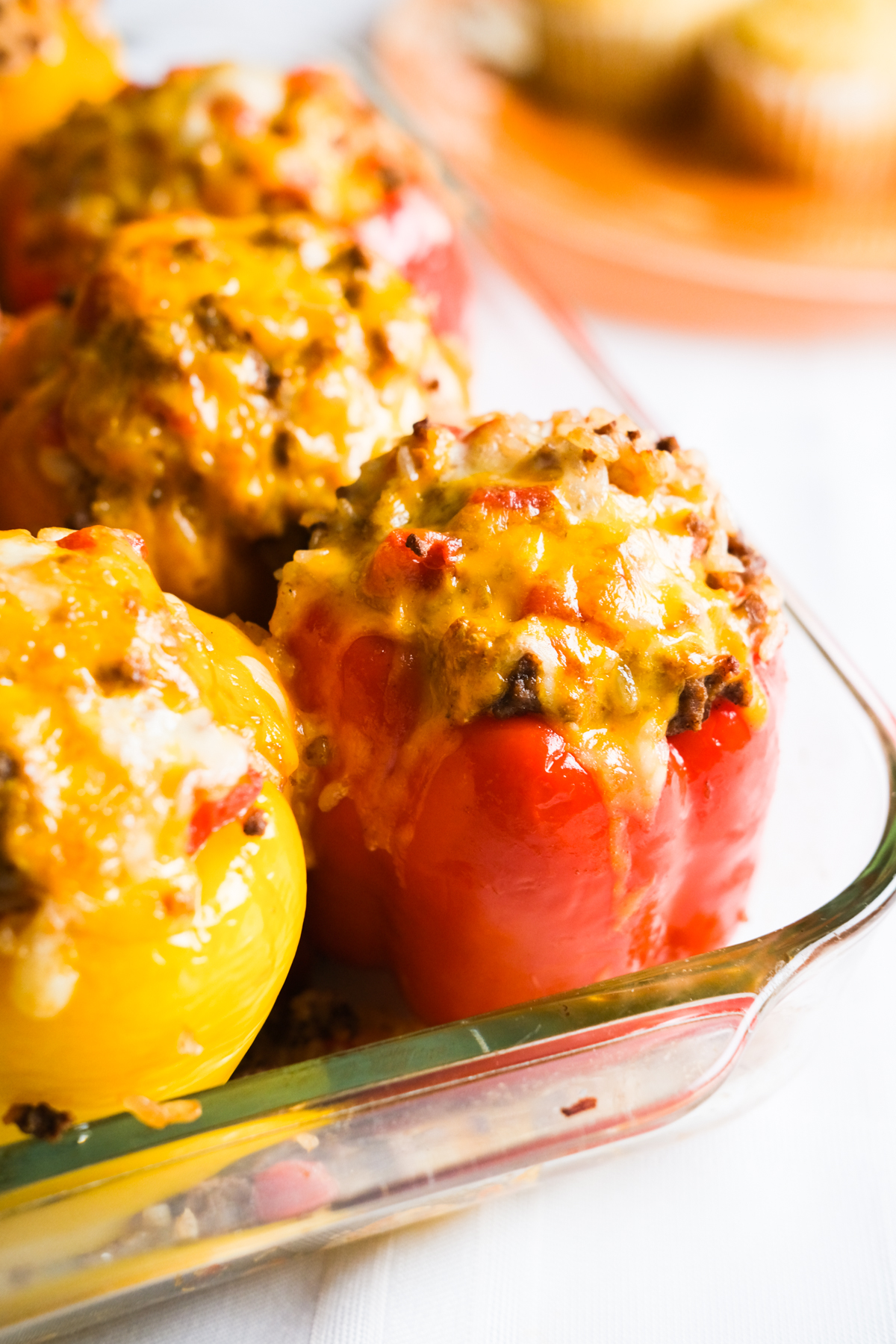 baked stuffed peppers in a pan with melty cheese