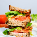 two halves of a blt sandwich stacked on a plate
