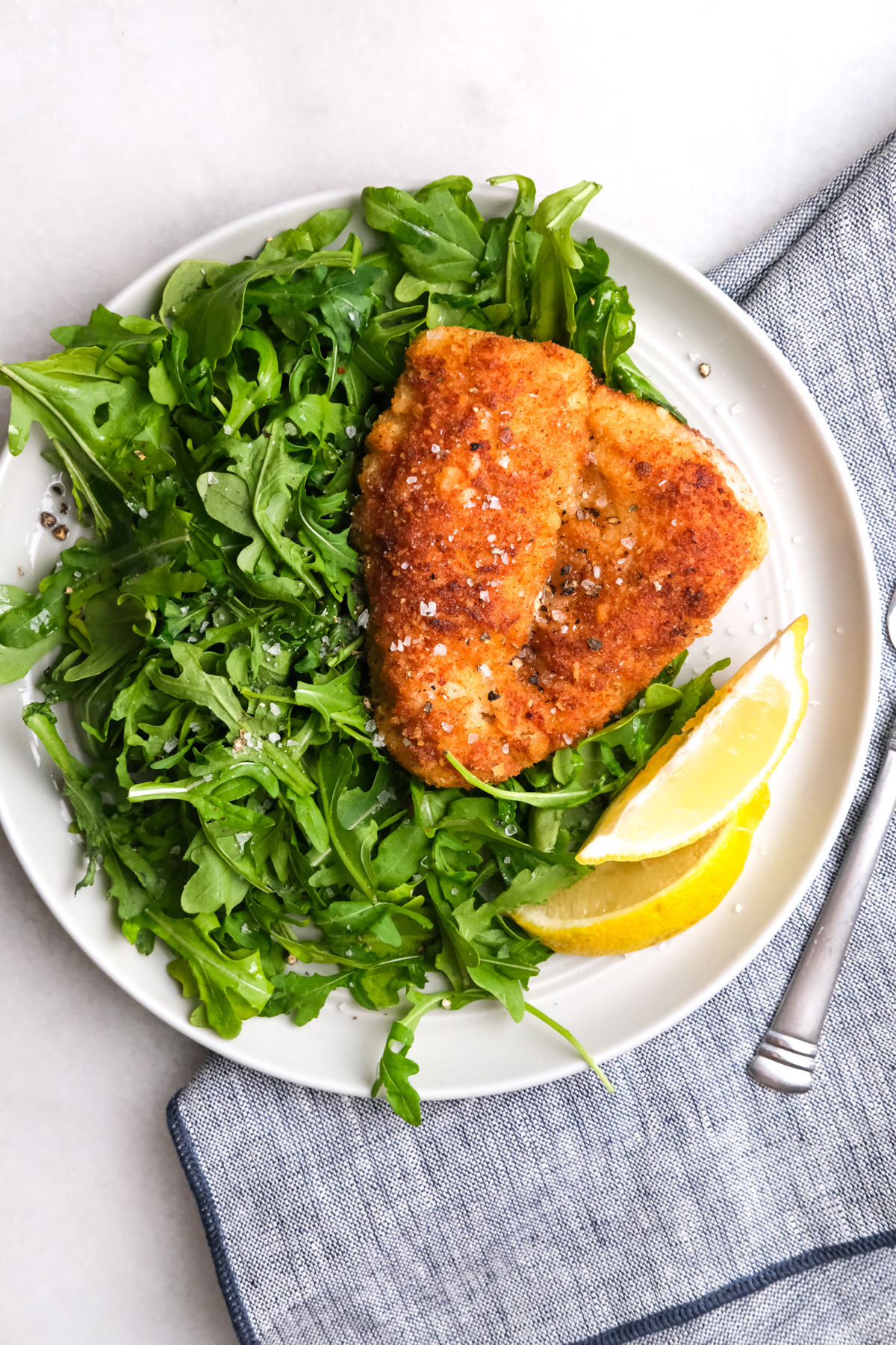 breaded chicken on a bed of arugula with lemon slices