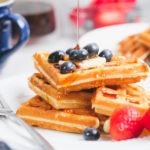 old fashioned waffles with berries and a maple syrup drizzle