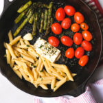 ingredients for a baked feta pasta in a skillet before mixing