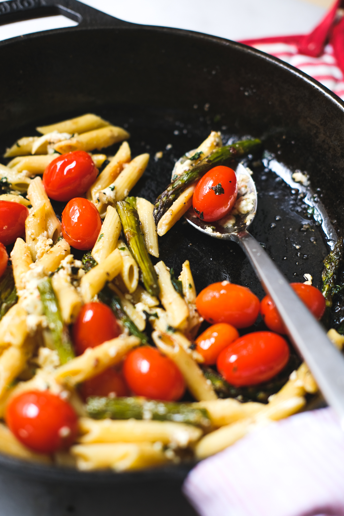 mixed ingredients for a baked feta pasta with tomatoes and asparagus