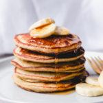 single stack of banana oatmeal pancakes with banana slices and syrup