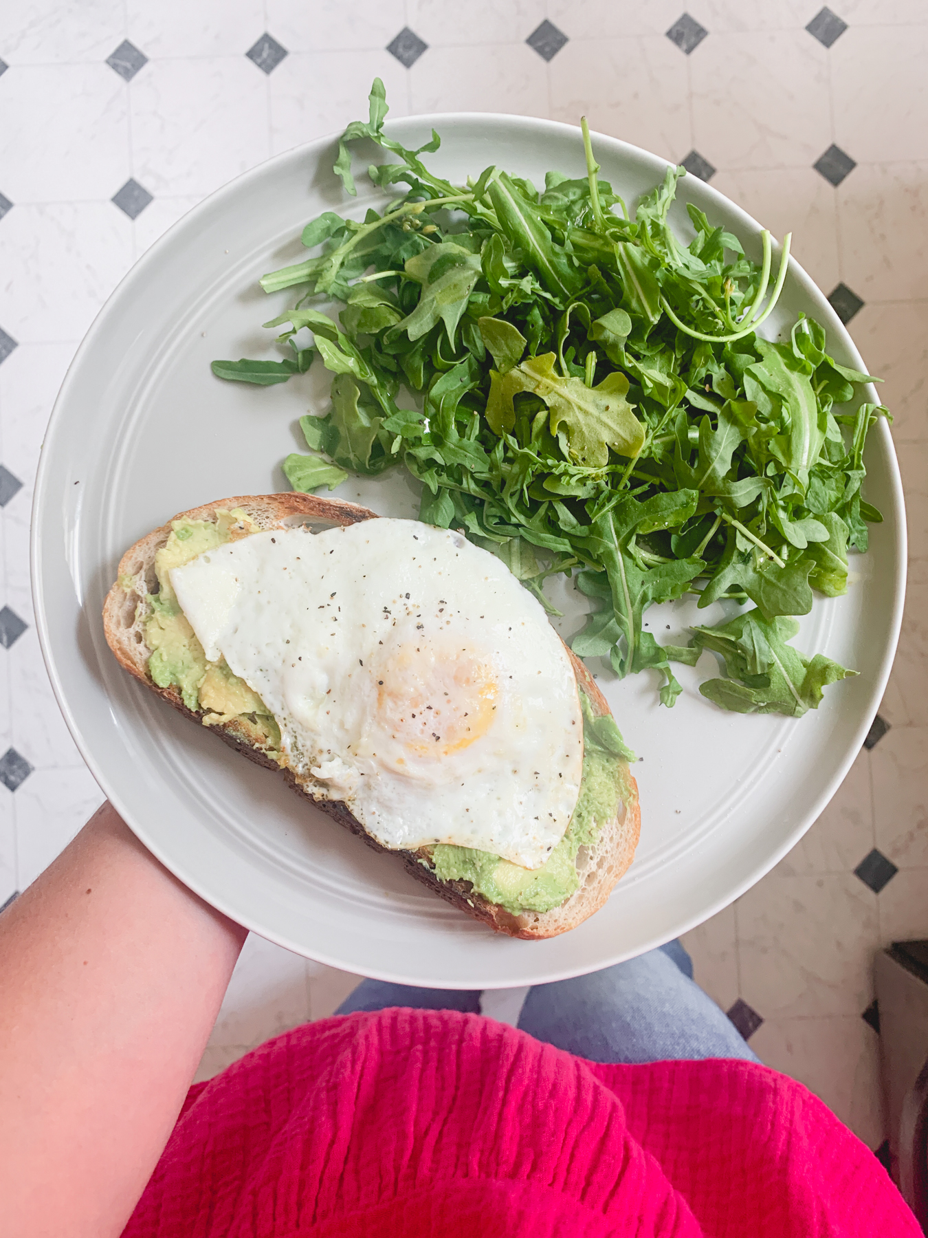 avocado toast with a fried egg and side salad