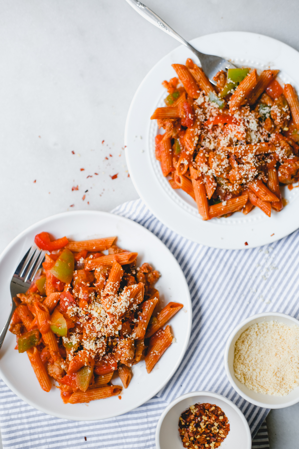 plates of sausage and pepper pasta with parmesan cheese