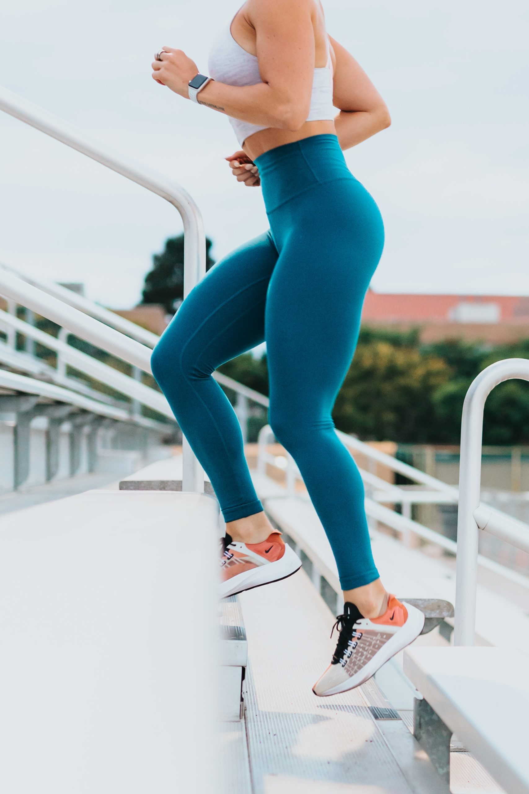 woman running up stadium stairs outside